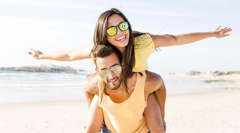 una pareja en la playa riéndose